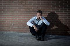 drug addict alone sitting on a wall